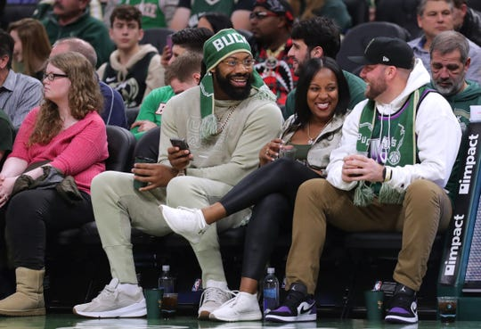 Packers linebacker Za'Darius Smith, second from left,  talks with a Bucks fan Tuesday night.