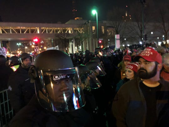 Rally attendees pass a line of Milwaukee police officers wearing masks and helmets as they leave the arena Jan. 14, 2020.
