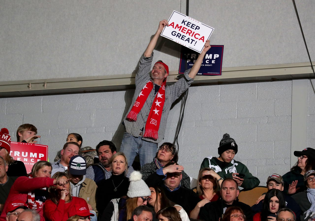 A man waves a sign as he waits for President Donald Trump to  speak at the UW-Milwaukee Panther Arena where the president held a campaign rally in Milwaukee on Tuesday, Jan. 14, 2020.