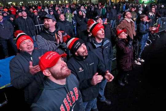 Donald Trump supporters watch the president's rally on a large screen in the overflow area outside the UW-Milwaukee Panther Arena on Tuesday.