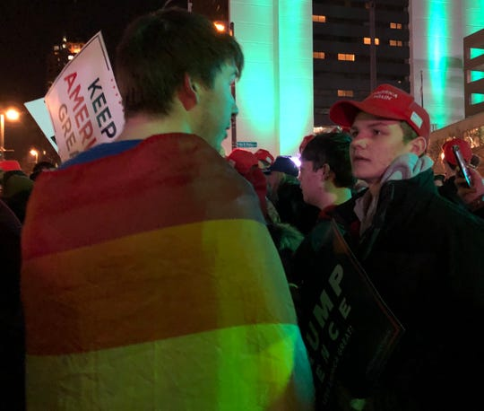Two students, one wrapped in a Pride flag and one wearing a Make America Great Again hat, argue about political discourse after the Trump rally in Milwaukee on Jan. 14, 2020.