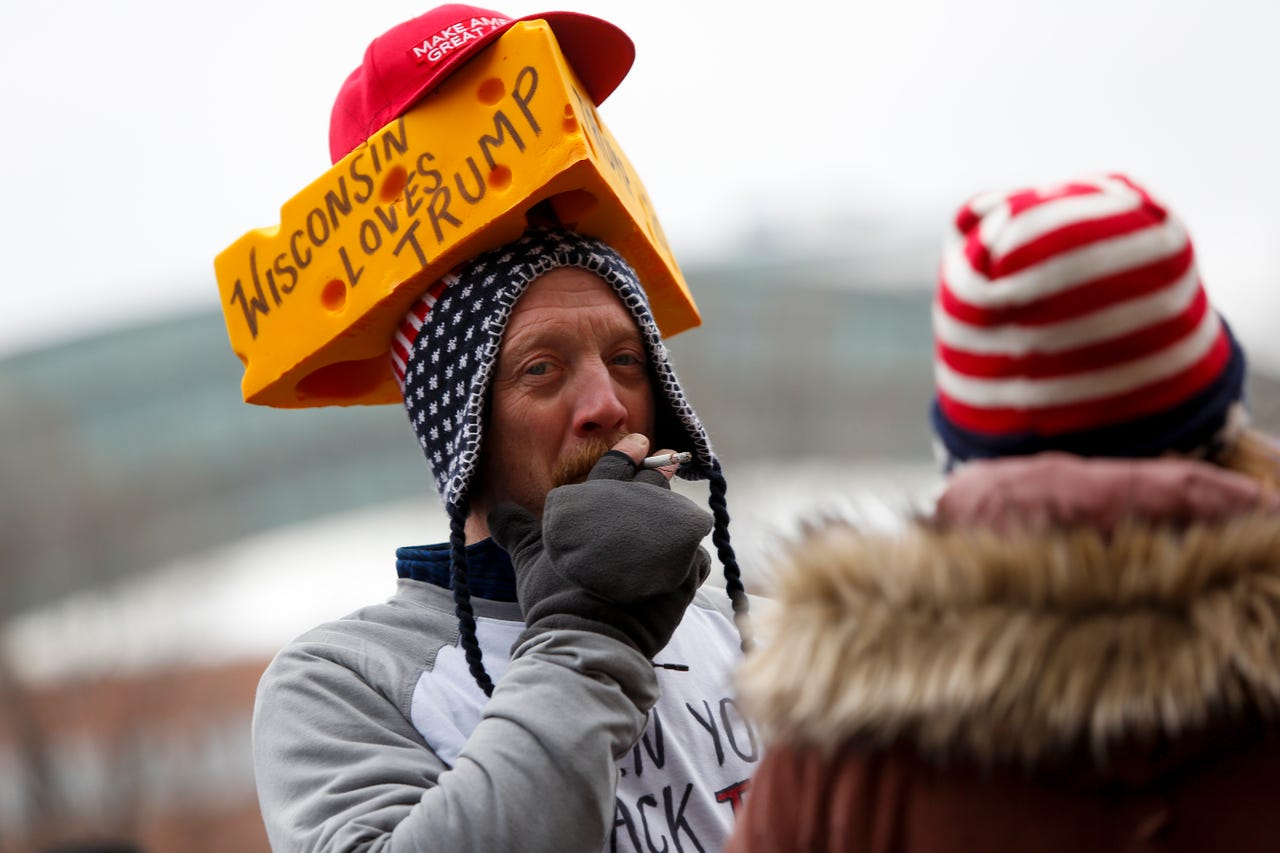An attendee smokes a cigarette, while waiting in line to attend a rally held by U.S. President Donald Trump's on January 14, 2020 at UW-Milwaukee Panther Arena in Milwaukee, Wisconsin. Trump, who is the third president to face impeached, now faces an impending trial in the Senate.