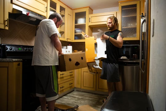 Marine veteran Ben Walter and his roommate Alan Demorett break down boxes after storing their groceries, Tuesday, Jan. 14, 2020, at the Alpha House in River Park.