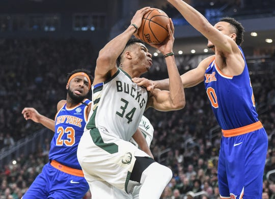 Jan 14, 2020; Milwaukee, Wisconsin, USA;  Milwaukee Bucks forward Giannis Antetokounmpo (34) drives to the basket between New York Knicks center Mitchell Robinson (23) and forward Kevin Knox II (20) in the second quarter at Fiserv Forum.