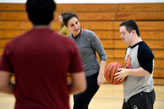 Denise Scalzitti, who coaches the integrated basketball team at Wayne Hills High School, helps a player at practice there on Jan. 14.