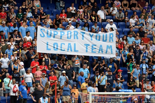 """The Sky Blue FC fans hold up a banner reading """"Support your local team"""" during a match against Reign FC at Red Bull Arena on Sunday, August 18, 2019, in Harrison."""