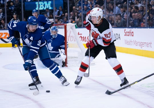 Jan 14, 2020; Toronto, Ontario, CAN; Toronto Maple Leafs center Auston Matthews (34) battles for a puck with New Jersey Devils left wing Jesper Bratt (63) during the first period at Scotiabank Arena.