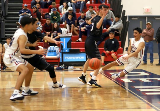 At right, freshman guard Alex Alfaro saves the basketball while airborne on the baseline. The Deming High Wildcats out-hustled the 6th-ranked Onate High Knights to claim a 49-46 District 3-5A victory on Tuesday at Deming High School.
