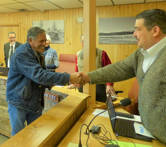 "Manuel ""Manny"" Madrono, who retired from the Solid Waste Department shakes Village Manager Tim Dodge's hand at the council meeting after receiving a plaque noting his service."