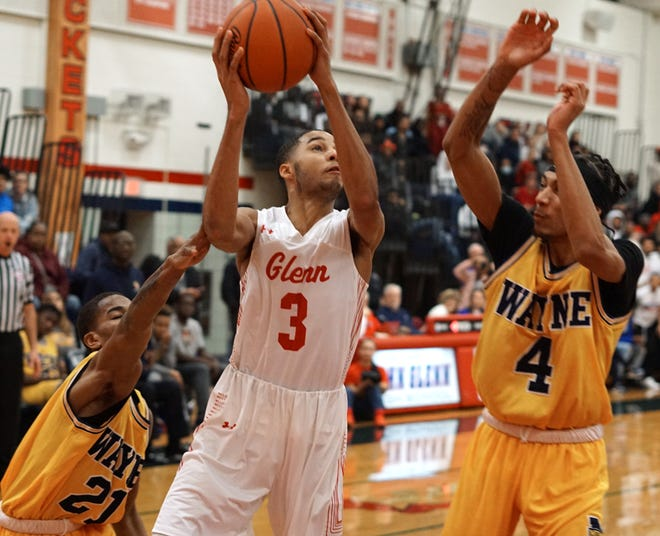 John Glenn's Deonte Pearson tries to get a shot up while being guarded by two Wayne Memorial players.