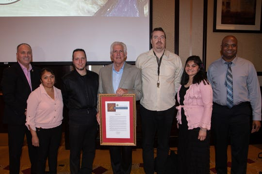 Richard Balocco, president and CEO of Desert Arc, displays the proclamation he presented to Desert Arc on its 60th Anniversary. Present are Glenn Miller, vice chair of the Desert Arc board of directors and mayor of Indio; client honoree Claudia; client honoree Matt; client honoree Brendan; client honoree Veronica and client honoree Kyle.