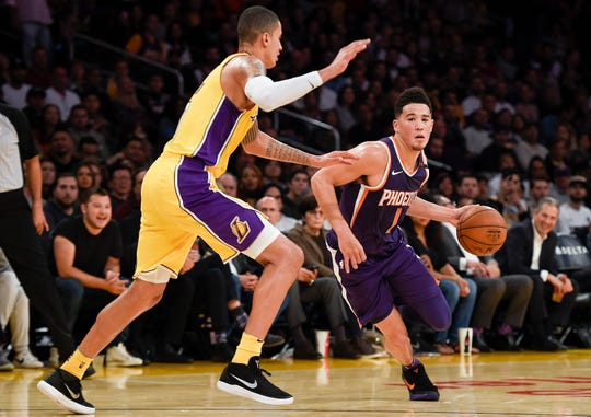 Phoenix Suns guard Devin Booker (1) drives the ball defended by Los Angeles Lakers forward Kyle Kuzma (0) during the third quarter at Staples Center in a 2017 game.