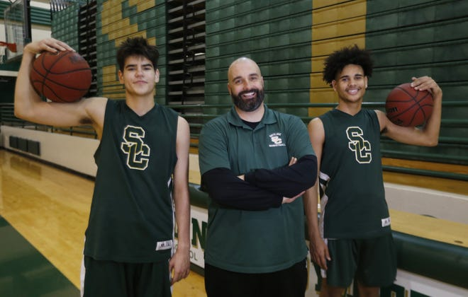 Skyline head coach James Capriotti poses for a picture with' Dayton Harris (R) and Dominic Capriotti at Skyline High School in Mesa.