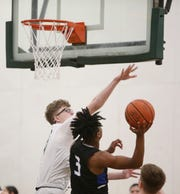Roosevelt's Dylan Craft blocks the shot of Wallkill's Justin Noelizaire during a boys basketball game on Tuesday.