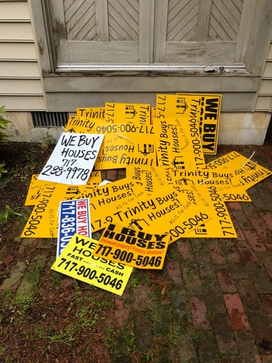 Dozens of bandit signs collected by Dennis Kunkle sit on a city sidewalk. Kunkle began removing the signs about a year ago in the WeCo district.