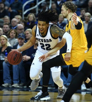 Nevada's Jazz Johnson drives against Wyoming's Jake Hendricks during Tuesday night's game at Lawlor Events Center.