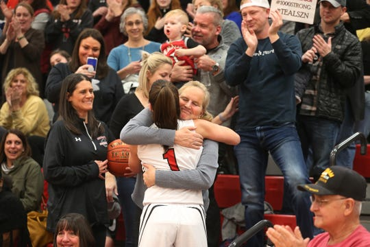 Baylee Teal, 1, center, goes into the stands to hug her mother Erica Teal, left, who is holding the 1,000 point ball, and Stephanie Gaitley, Fordham University women's basketball head coach, right, after she scored her 1,000 varsity point in the second quarter during their matchup against Mendon at Penfield High.