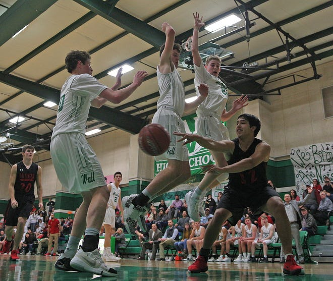 Ryan Elliott, lower right, dishes a pass for Ballinger during a game against Wall on Tuesday, Jan. 14, 2020.