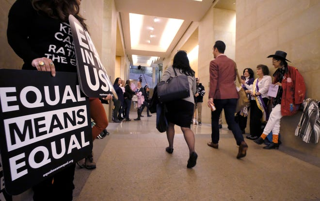 Equal Rights Amendment supporters yell encouragement to two legislators as they walk down a hallway inside the state Capitol in Richmond  Tuesday, Jan. 14.