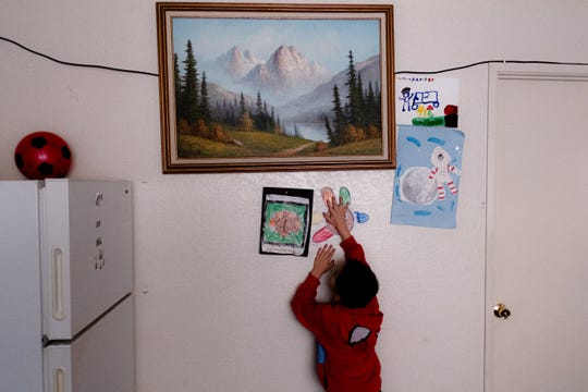 """Kender Ricardez Tobón, de 5 años, pega en la pared de su hogar un dibujo que hizo en la escuela. vive en un complejo de pequeños departamentos en el lado este de Salinas con su abuela Eufemia """"Jenni"""" Aguilar."""