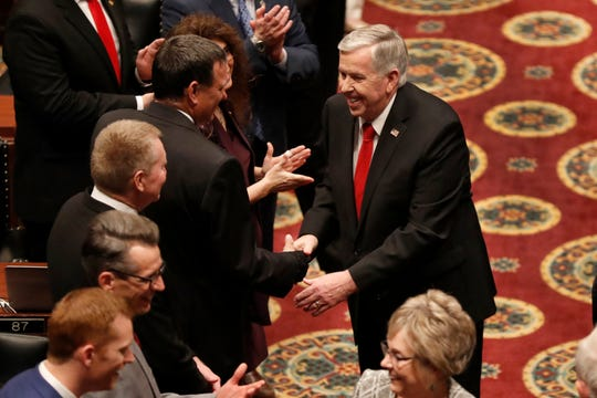 Missouri Gov. Mike Parson, right, shakes hands with lawmakers as he enters the House chamber to deliver the State of the State address Wednesday, Jan. 15, 2020, in Jefferson City, Mo.