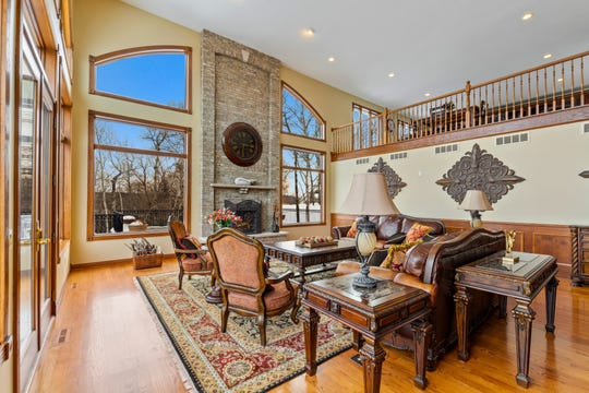 The vaulted two-story great room features floor-to-ceiling windows that overlook the lake.
