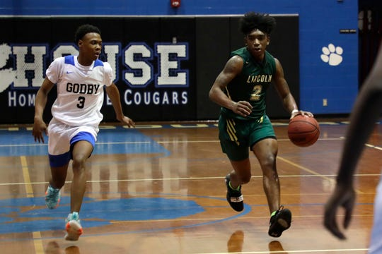 Lincoln senior guard Zae Wiggins dribbles up the court as Lincoln's boys basketball team beat Godby 68-60 on Jan. 14, 2020.