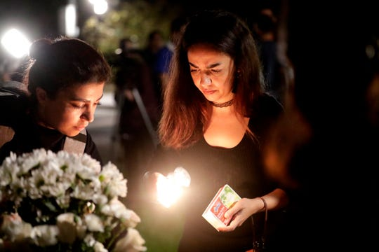 Maryam Takalou, a member of the Iranian Student Organization at Florida State University, lights candles at a vigil honoring the 176 lives lost in the crash of flight PS752.