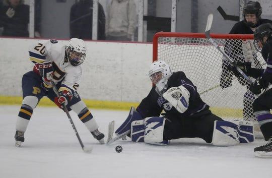 John Jay Cross River goalie Nick Petrella blocks a shot by Michael Mitrione of Pelham during a varsity hockey game at the Ice Hutch in Mount Vernon Jan. 14, 2020. John Jay defeated Pelham 3-2.