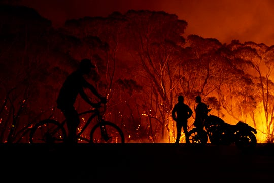 Residents look on as flames burn through bush on January 4, 2020 in Lake Tabourie, Australia.