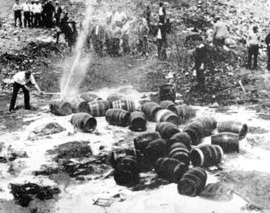 FILE - In this June 18, 1931, file photo beer barrels are destroyed by prohibition agents at a dump in New York City. The federal government, as well as state and local authorities, spent huge sums on enforcement yet never allocated sufficient resources to do the job effectively. Bootleggers awash in cash bribed judges, politicians and law enforcement officers to let their operations continue. (AP Photo, File)