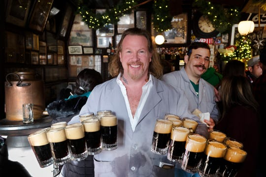 In this Dec. 27, 2019 photo, Gregory de la Haba serves 20 mugs of beer for a table of customers in McSorley's Old Ale House in New York. Located in Manhattan's Lower East Side, McSorley's opened in the mid-19th century and remained open as a speakeasy during Prohibition. The Prohibition Era, which lasted from Jan. 17, 1920, until December 1933, is now viewed in popular culture as a failed experiment that glamorized pervasive illegal drinking. (AP Photo/Mark Lennihan)