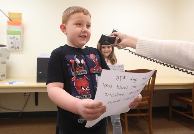 Dresden Elementary School students Andy Marsh, left, and Piper Clifford read an announcement at the start of school on Wednesday. They are in Selena Emerson's first-grade class, which is raising money for Australian animals injured in the massive wildfires that have burnt much of the country.