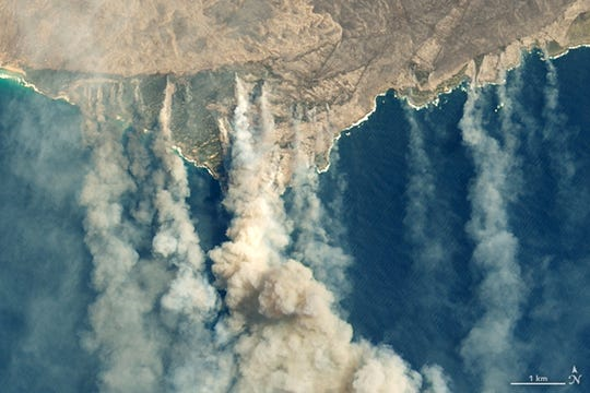 A satellite image from the NASA Earth Observatory shows burned land and thick smoke over Kangaroo Island, Australia, on Jan. 9.