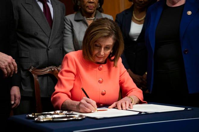 Die Parlamentssprecherin Nancy Pelosi verwendet eine Vielzahl von Stiften, um Amtsenthebungsverfahren gegen Präsident Donald Trump zu unterzeichnen.