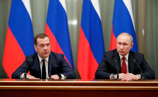 Russian President Vladimir Putin, right, and Prime Minister Dmitry Medvedev meet with members of the government in Moscow on Jan. 15, 2020.