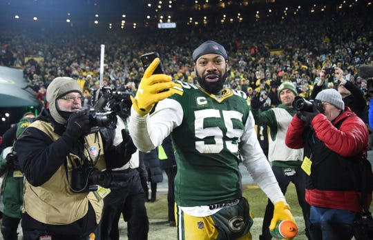 Green Bay Packers outside linebacker Za'Darius Smith (55) uses a cell phone as he leaves the field after defeating the Seattle Seahawks in a NFC Divisional Round playoff football game at Lambeau Field.
