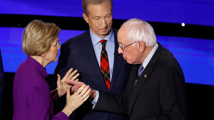 Democratic presidential candidate Sen. Elizabeth Warren, D-Mass., left and Sen. Bernie Sanders, I-Vt., talk Tuesday, Jan. 14, 2020, after a Democratic presidential primary debate hosted by CNN and the Des Moines Register in Des Moines, Iowa. Candidate businessman Tom Steyer looks on (AP Photo/Patrick Semansky) ORG XMIT: IAKJ178