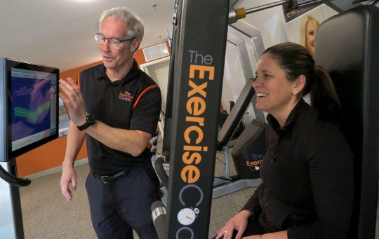 Peter Dunphy, owner of Exercise Coach in Fair Haven, sets up Alexandria Everett, Rumson, to complete a seated row exercise Thursday, January 16, 2020.  The facility uses computer aided fitness machines for an efficient workout to build and strengthen muscles.