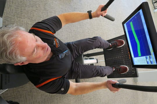 Peter Dunphy, owner of Exercise Coach in Fair Haven, demonstrates a leg press machine Thursday, January 16, 2020.  The facility uses computer aided fitness machines for an efficient workout to build and strengthen muscles.