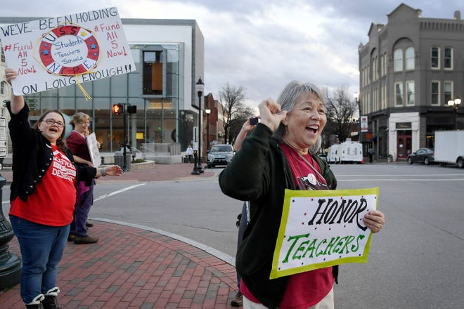 """Joanne Robert, a 7th grade math teacher at Asheville Middle School, encourages drivers to honk their horns during the """"Our Schools Deserve Funds Now"""" rally at Vance Memorial in downtown Asheville January 15, 2020. """"We are the profession that makes every profession possible,"""" said Robert, who is in her 35th year of teaching."""