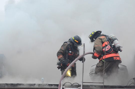 Firefighters battle the fire from the roof.