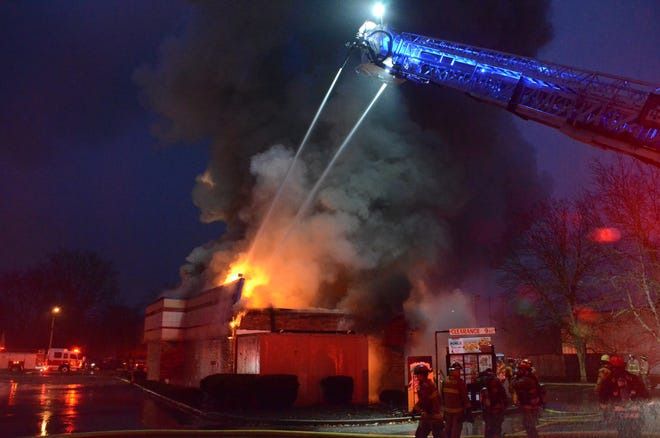 Firefighters pour water on the fire Wednesday at Kentucky Fried Chicken in Pennfield.