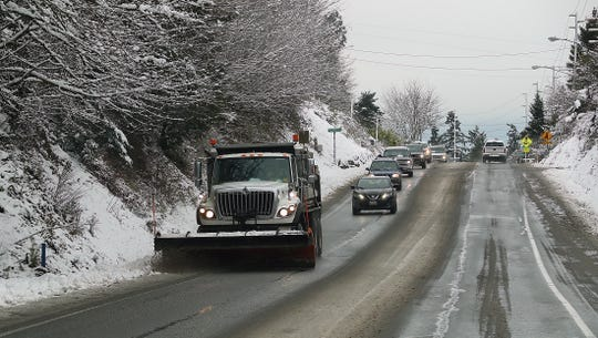 A snow plow scrapes the shoulder of Viking Avenue in Poulsbo on Wednesday, Jan. 15, 2020.