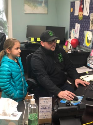Chad, an estimating manager at Emerald Installation, and his daughter Brooke, in the office during a day in which Kitsap schools were canceled. The company has a family-friendly policy, allowing kids to accompany their parents to work on days when school is called off and no childcare is available.