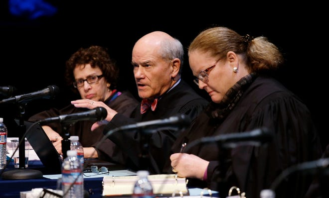 FILE - In this Nov. 15, 2016, file photo Washington Supreme Court Justice Charles K. Wiggins, second left, speaks as fellow Justices Sheryl Gordon McCloud, left, and Mary E. Fairhurst listen during arguments in Bellevue, Wash. Wiggins, 72, announced Thursday, Jan. 16, 2020, he will retire at the end of March. Wiggins was first elected to the court in 2010.