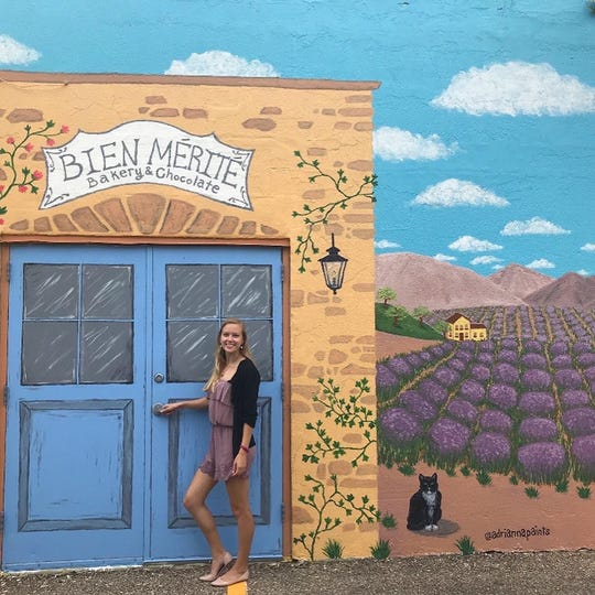 The Bien Merite mural features a lavender field, blue skies and hills on a French countryside. It is located near Bien Merite Bakery and Chocolate on Staples Street and Morgan Avenue.