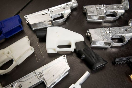 Gun parts at Defense Distributed, a Texas-based company developing and publishing open-source gun designs for 3D printing and manufacture, surround a copy of the Liberator, a 3D-printed plastic gun.