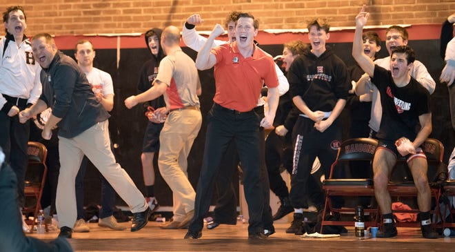 Haddonfield High School's wrestling coach Eric Hamrick, center, celebrates with his team after Haddonfield's Dan Flood pinned Sterling's Stephan Johnson to win the 285 lb. bout of the wrestling match held at Haddonfield High School on Wednesday, January 15, 2020.