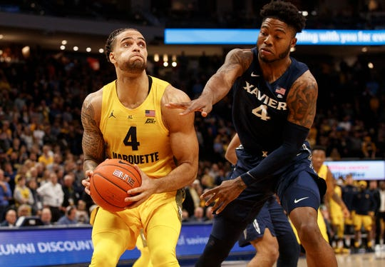 Jan 15, 2020; Milwaukee, Wisconsin, USA; Marquette Golden Eagles forward Theo John (4) looks to shoot against Xavier Musketeers forward Tyrique Jones (4) during the first half at Fiserv Forum.